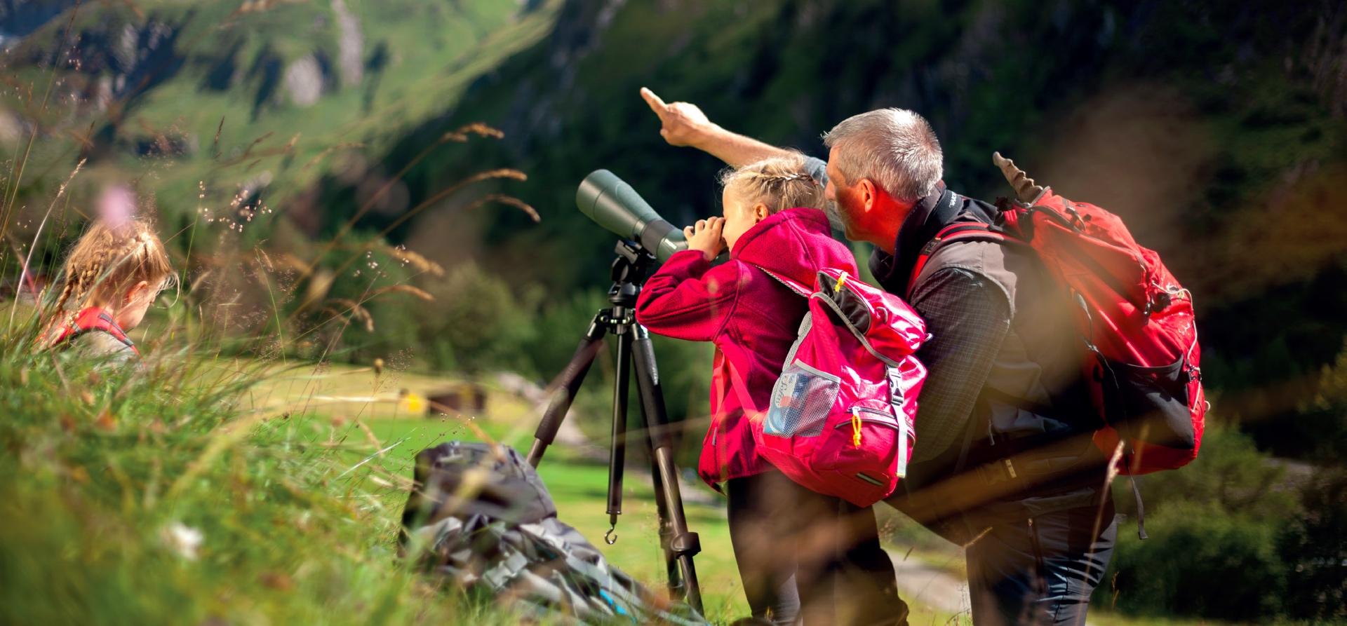 Naturbeobachtung durch das Monokular muss geübt werden. Der Nationalparkranger zeigt dem Jungen wie es funktioniert © Nationalpark Hohe Tauern: Martin Kurzthaler, Martin Lugger