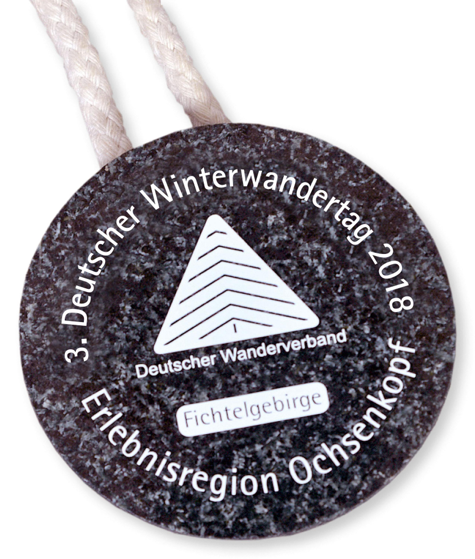 Die Winterwandertagsplakette 2018 besteht aus dunklem Prote- robas, eine für die Region typische Gesteinsart, die früher zur Glas- herstellung diente und bis 2009 am Ochsenkopf abgebaut wurde.